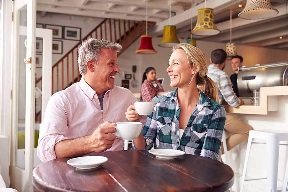 Man and woman on a coffee date smiling