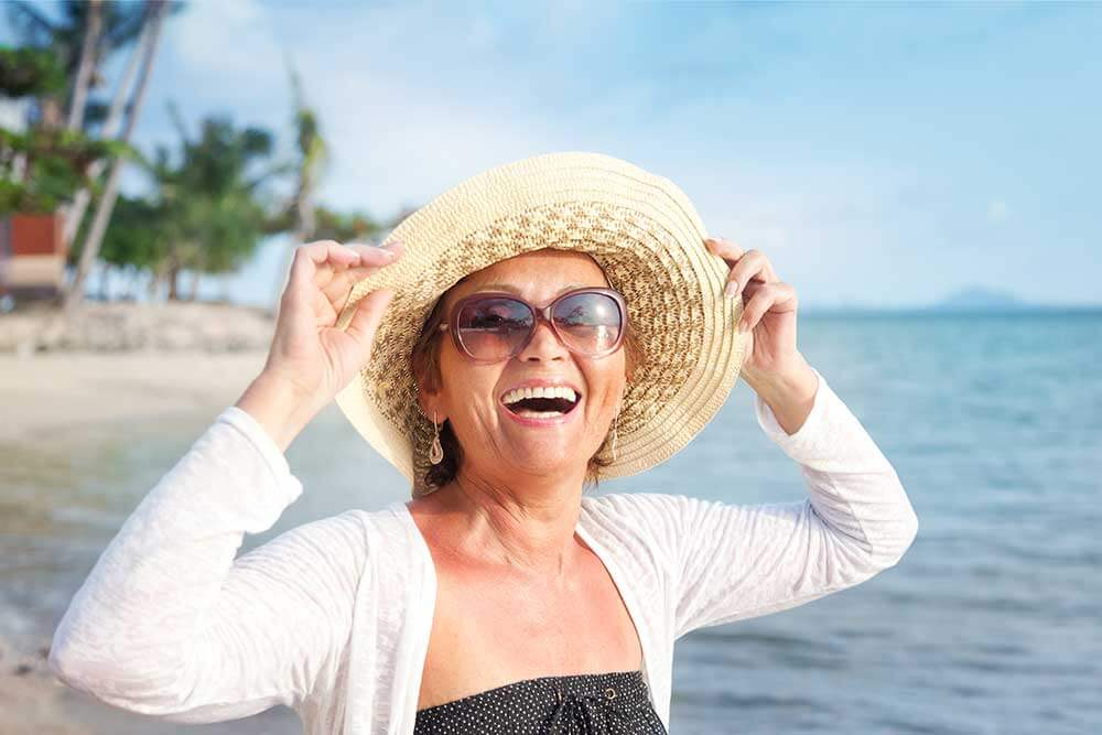 Woman walking on beach holding her had on her head